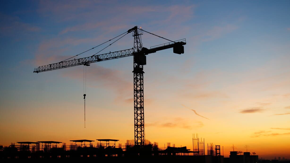 Construction cranes with sunset